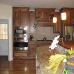 The Lee Kitchen with custom cabinetry, granite counter tops and wall appliances.